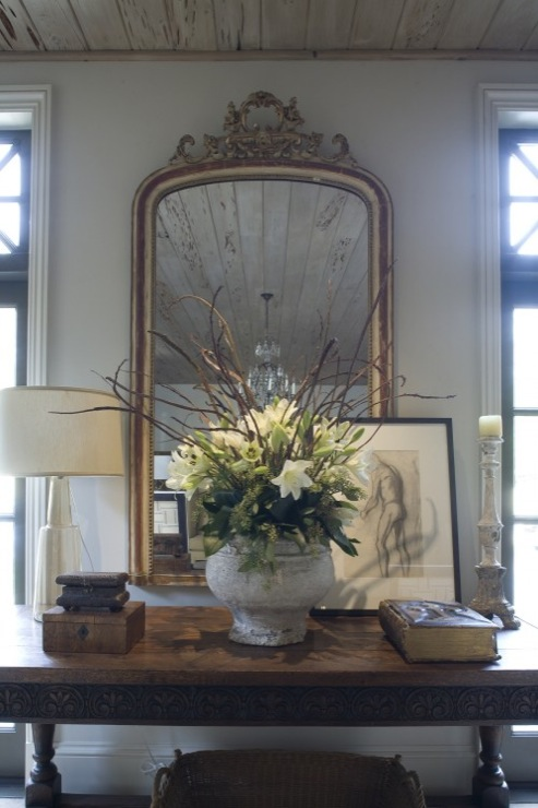 console with flowers and mirror above basket below