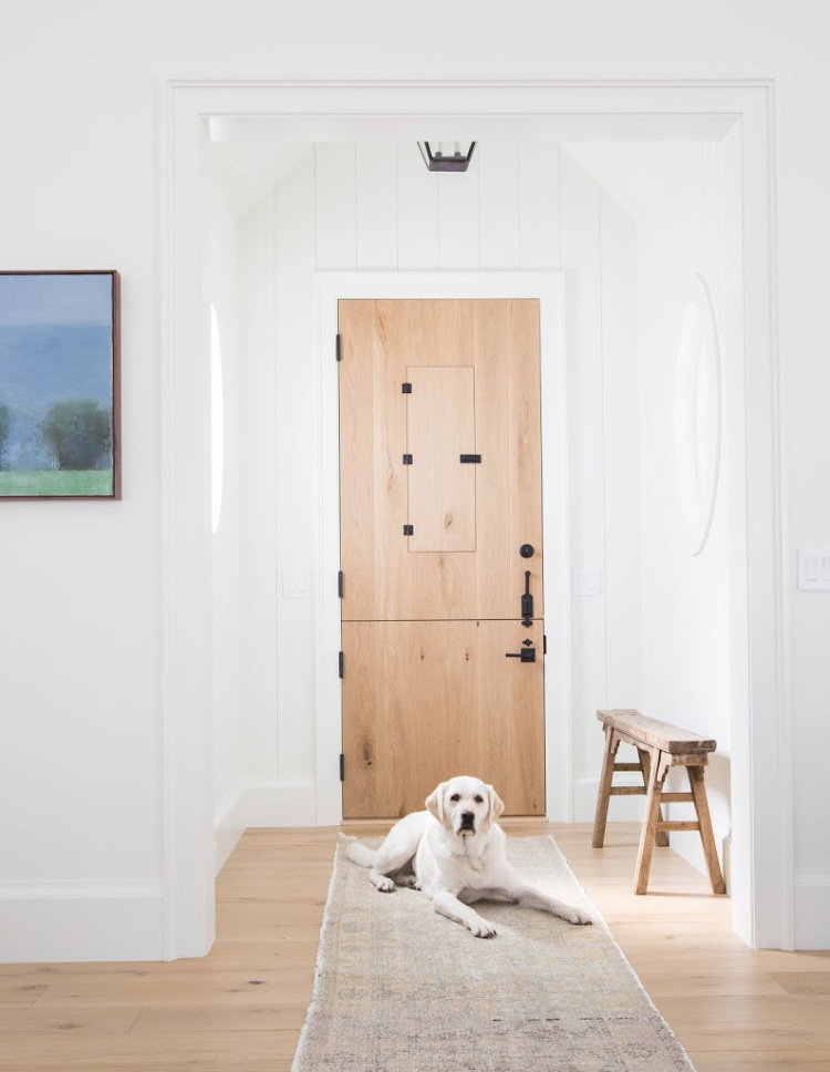 blonde wood Dutch door with bench in foyer by Amber Interiors